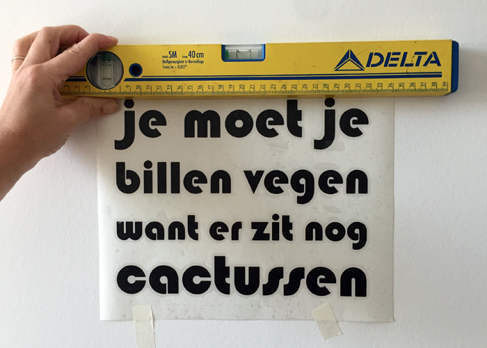 meet of de muursticker recht hangt met een waterpas